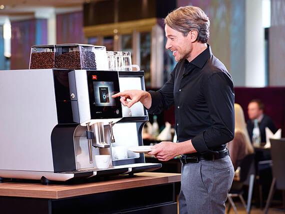 Mann bedient Gastro Kaffeemaschine an Hotelbar